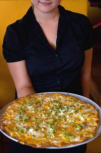 Waitress serving a cheese crisp at El Charro