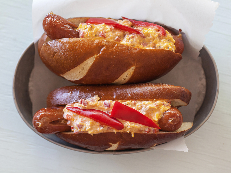 Pimento Cheese Hot Dog with Red Peppers on a Pretzel Bun