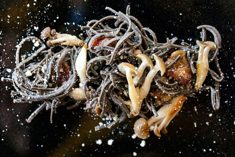 black pasta carbonara with exotic beech mushrooms.
