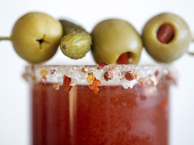 A salty, spicy spice blend made with Vegetarian bacon bits line the rims of a Bloody Mary. Fun holiday drink rim ideas and photography by Jackie Alpers for the FoodNetwork.com.